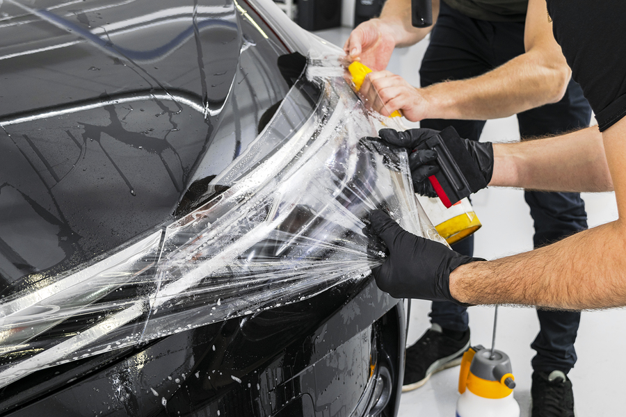 applying a protective film to the car with tools for work.