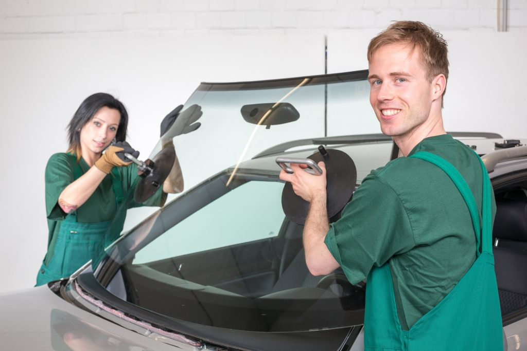 man and woman installing windshield